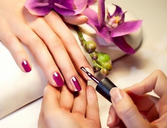 紫のネイルを塗る手