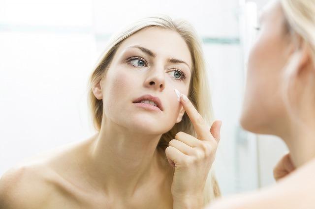 鏡で肌チェックする女性