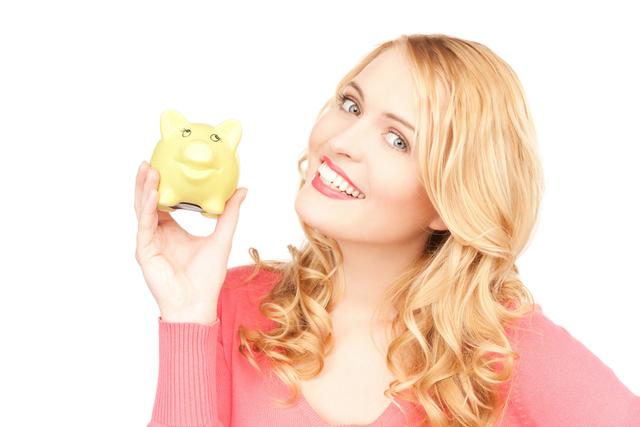 貯金箱を持って笑う女性