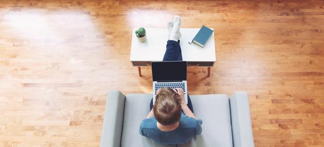 ウッドカーペットのある部屋でパソコンを打つ人