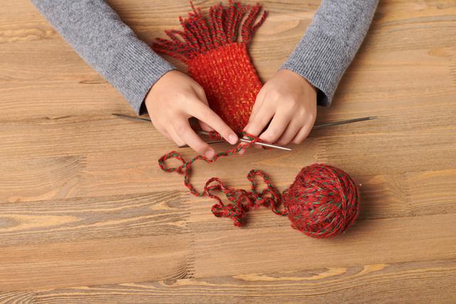 赤いマフラーを編む手