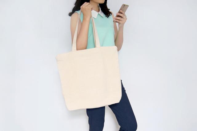 携帯片手にトートバッグを持つ女性