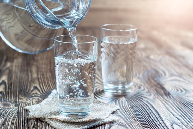 コップに水を注ぐ人